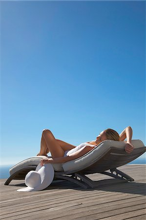 Woman sunbathing on a sun lounger against blue sky Stock Photo - Rights-Managed, Code: 822-03406647