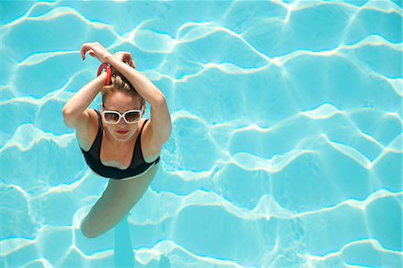 Elevated view of a woman standing in a swimming pool with arms crossed over head Stock Photo - Rights-Managed, Code: 822-03407025