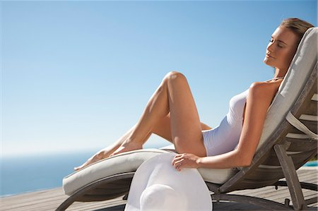 Woman sunbathing on a sun lounger against blue sky Stock Photo - Rights-Managed, Code: 822-03407075