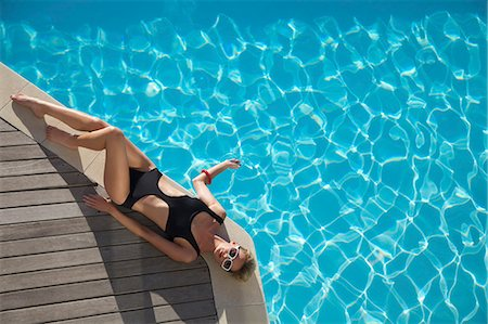 Elevated view of a woman sunbathing on the edge of a swimming pool Stock Photo - Rights-Managed, Code: 822-03407095