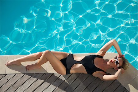 Elevated view of a woman sunbathing on the edge of a swimming pool Stock Photo - Rights-Managed, Code: 822-03407120