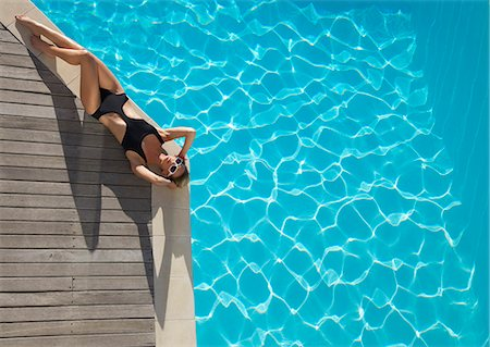 Elevated view of a woman sunbathing on the edge of a swimming pool Stock Photo - Rights-Managed, Code: 822-03407134