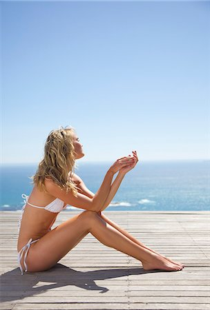 Young woman sunbathing with ocean in the background Stock Photo - Rights-Managed, Code: 822-03407141