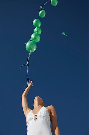 release - Woman releasing green balloons in a cloudeless sky - low angle view Stock Photo - Rights-Managed, Code: 822-03407164