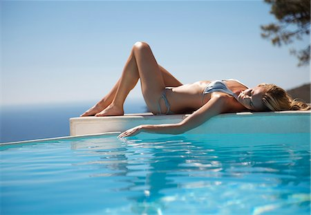Woman sunbathing by a swimming pool with ocean in the background Stock Photo - Rights-Managed, Code: 822-03407165