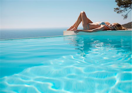 Woman sunbathing by a swimming pool with ocean in the background Stock Photo - Rights-Managed, Code: 822-03407161