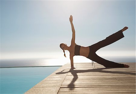 Young woman practicing yoga by a swimming pool with ocean in the background Stock Photo - Rights-Managed, Code: 822-03407178