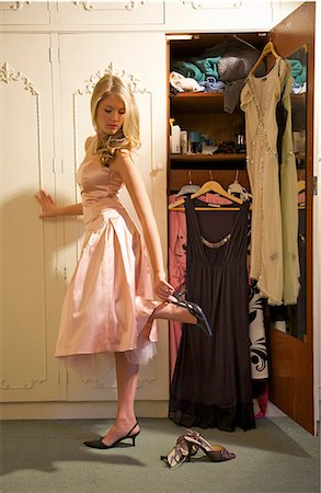 Young woman standing in front of open wardrobe putting on shoes Stock Photo - Rights-Managed, Code: 822-03407191