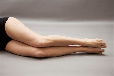 Woman lying on side with liposuction markings on her thigh, headless Stock Photo - Rights-Managed, Code: 822-03485167
