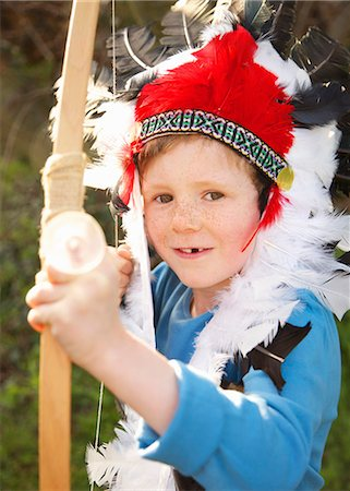 Boy wearing Indian chief feather headdress holding bow and arrow Stock Photo - Rights-Managed, Code: 822-03485178