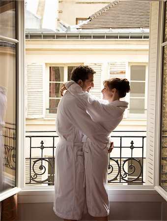 Couple hugging in front of an open window Stock Photo - Rights-Managed, Code: 822-03485229