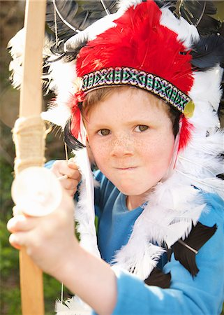 Boy wearing Indian chief feather headdress holding bow and arrow Stock Photo - Rights-Managed, Code: 822-03485234