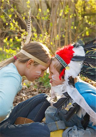 Boy and girl wearing Indian feather headdresses sitting face to face Stock Photo - Rights-Managed, Code: 822-03485327
