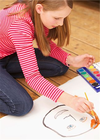 Girl kneeling on floor painting with watercolours Stock Photo - Rights-Managed, Code: 822-03485353