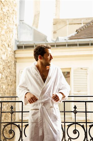 Man in bathrobe leaning on a balcony Stock Photo - Rights-Managed, Code: 822-03485385