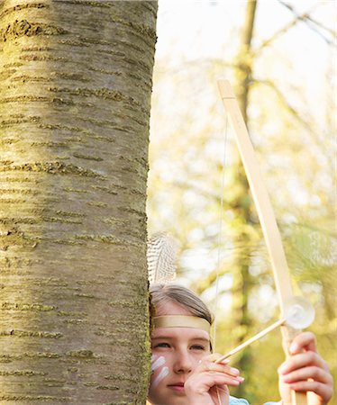 Girl hiding behind tree wearing Indian feather headdress holding bow and arrow, close up Stock Photo - Rights-Managed, Code: 822-03485437