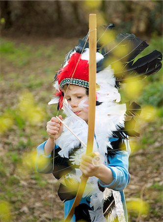 Boy wearing Indian chief feather headdress holding bow and arrow Stock Photo - Rights-Managed, Code: 822-03485465