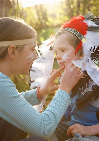Girl wearing Indian headdress applying paint on boy face Stock Photo - Rights-Managed, Code: 822-03485466