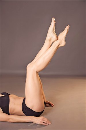 Woman lying on her back with legs raised wearing black underwear, headless Stock Photo - Rights-Managed, Code: 822-03485482