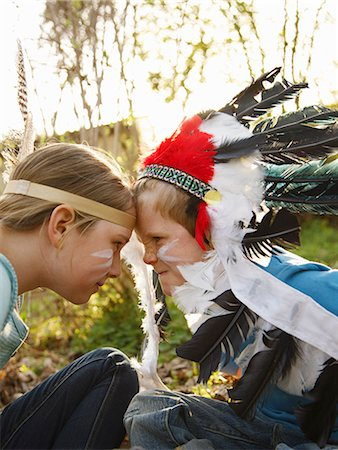 Boy and girl wearing Indian feather headdresses sitting face to face Stock Photo - Rights-Managed, Code: 822-03485497
