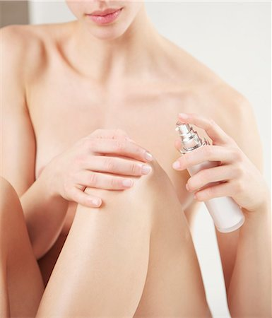 Close up of a nude woman applying cosmetic cream on her knee Stock Photo - Rights-Managed, Code: 822-03485555