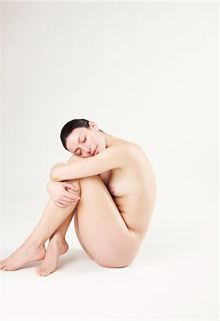 Portrait of a nude woman hugging her knees Stock Photo - Rights-Managed, Code: 822-03485585