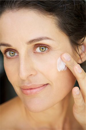 prevention - Close up of a woman applying cosmetic cream Stock Photo - Rights-Managed, Code: 822-03485588