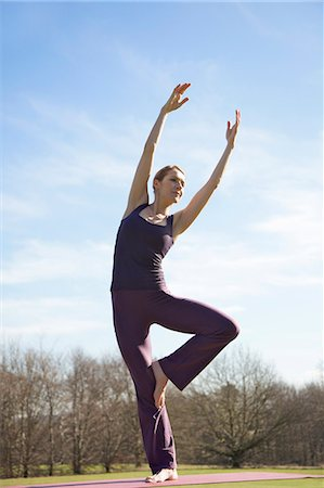 Woman practicing yoga in park Stock Photo - Rights-Managed, Code: 822-03485610