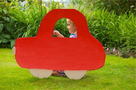 Girl Kneeling behind Cardboard Cut Out in Shape of Car Stock Photo - Rights-Managed, Code: 822-03601557