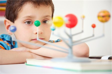 Boy Inspecting Solar System Model Stock Photo - Rights-Managed, Code: 822-03601647