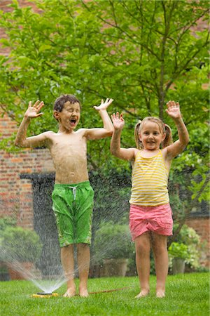 Boy and Girl Playing with Sprinkler Stock Photo - Rights-Managed, Code: 822-03601674