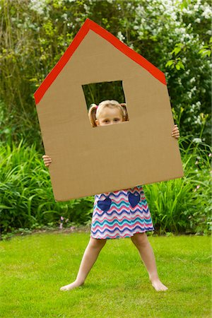 Girl Looking Out from the Window of Cardboard Cut Out in Shape of House Stock Photo - Rights-Managed, Code: 822-03601705