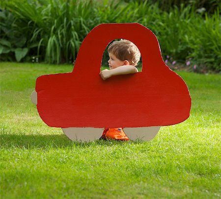 Young Boy Kneeling behind Cardboard Cut Out in Shape of Car Stock Photo - Rights-Managed, Code: 822-03601866