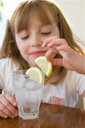 Girl Playing with Slice of Lemon over a Glass of Water Stock Photo - Rights-Managed, Code: 822-03602067