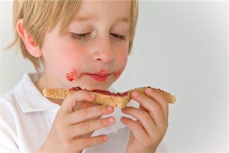 Boy Eating Jam on Toast Stock Photo - Rights-Managed, Code: 822-03602104