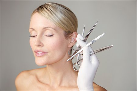 Doctor's Hand Holding Surgical Instruments in front of Woman's Face Stock Photo - Rights-Managed, Code: 822-03780858