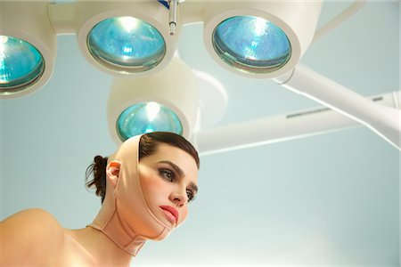 Woman with Elastic Bandage on Face and Neck under Surgical Lamp - Low angle view Stock Photo - Rights-Managed, Code: 822-03780896