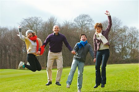 recreation - Smiling Family Holding Hands and Jumping in Park Stock Photo - Rights-Managed, Code: 822-03781067