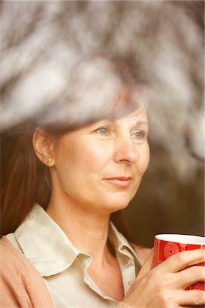 Woman Holding Coffee Cup behind Window Stock Photo - Rights-Managed, Code: 822-03781075