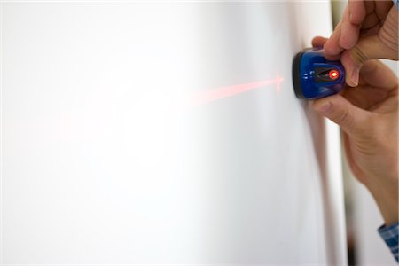 Man's Hands Holding Laser Level against White Wall Stock Photo - Rights-Managed, Code: 822-03781108