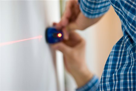 Man's Hands Holding Laser Level against White Wall Stock Photo - Rights-Managed, Code: 822-03781109