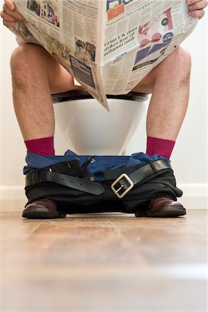 Man Sitting on Toilet Reading Newspaper Stock Photo - Rights-Managed, Code: 822-03781110