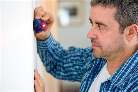 Profile of Man Holding Laser Level against White Wall Stock Photo - Rights-Managed, Code: 822-03781111
