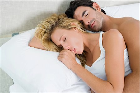 High angle view of a young man and a mid adult woman lying on the bed Stock Photo - Rights-Managed, Code: 837-02378166