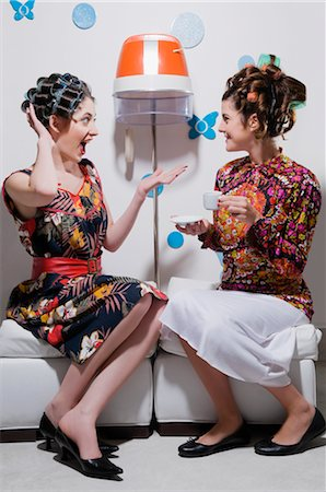 Two young women sitting in a hair salon and looking at each other Stock Photo - Rights-Managed, Code: 837-02378565