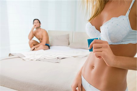 Mid section view of a mid adult woman holding a condom with a young man in the background Stock Photo - Rights-Managed, Code: 837-02378668