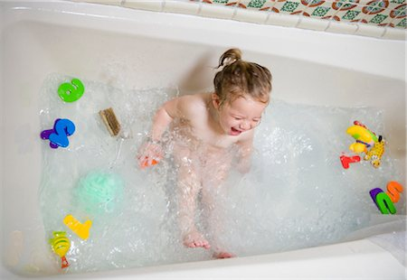 High angle view of a baby girl sitting in a bathtub and laughing Stock Photo - Rights-Managed, Code: 837-02378800