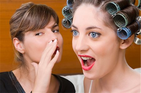 Close-up of a young woman whispering into the ear of another young woman Stock Photo - Rights-Managed, Code: 837-02379240