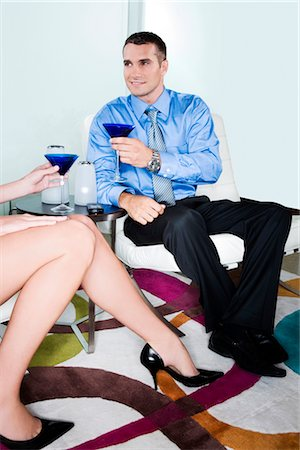 Young man holding a glass of cocktail and looking at a woman sitting beside him Stock Photo - Rights-Managed, Code: 837-02380202
