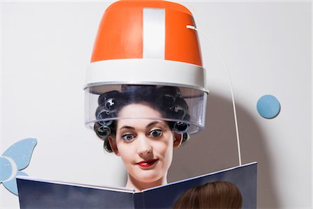 Close-up of a young woman sitting under hair dryer and reading a book Stock Photo - Rights-Managed, Code: 837-02380973